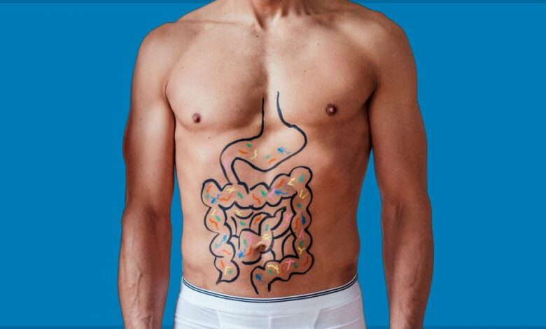 Man with an illustration of his abdomen and intestines with colorful bacteria on blue background