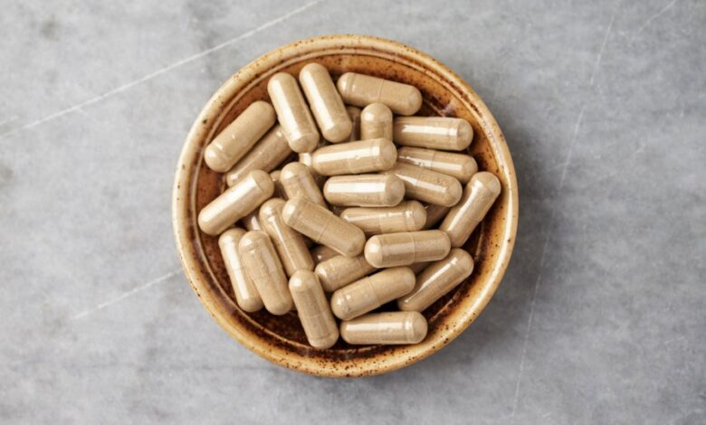 Ashwagandha (Withania somnifera) capsules in a bowl on bright stone countertop